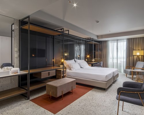 A well furnished bedroom with balcony and ocean view.