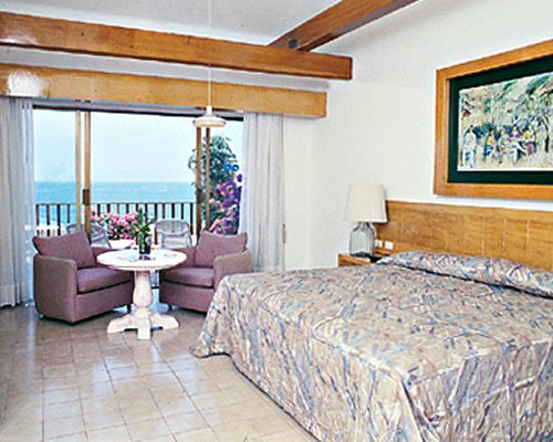 A well furnished bedroom with a king bed and balcony.
