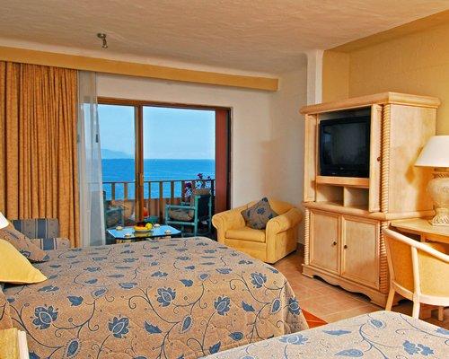 A well furnished bedroom with two beds television and the ocean view.