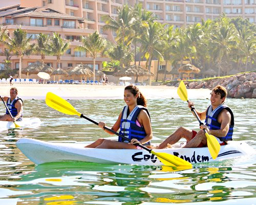 View of people kayaking alongside Hotel Hola Puerto Vallarta Club.