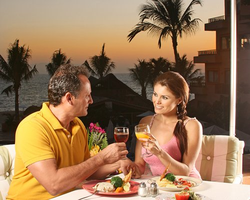 A couple at the outdoor dining having beverage and food alongside the bay with palm trees.