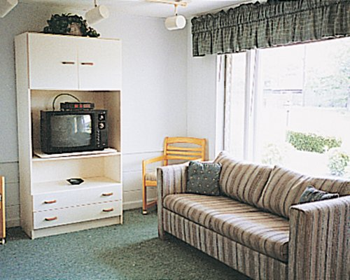 A well furnished living room with television double pull out sofa and an outside view.