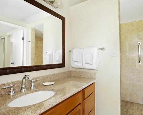 A bathroom with shower stall and closed sink vanity.
