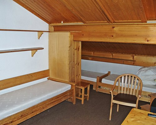 A wooden sloped bedroom with multiple beds.