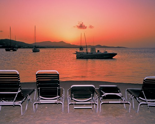 View of the beach with boats alongside patio chairs at dusk.