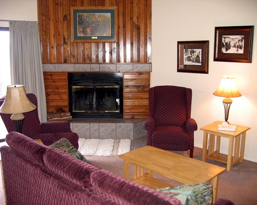 A well furnished living room with a double pull out sofa and fireplace.