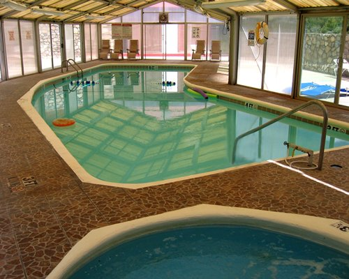 An indoor swimming pool and hot tub with an outside view.