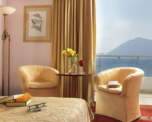 A well furnished bedroom with two sofas and a balcony.