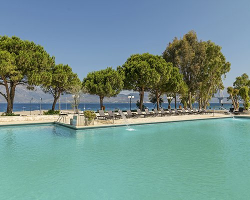 A large outdoor swimming pool with chaise lounge chairs alongside the waterfront.