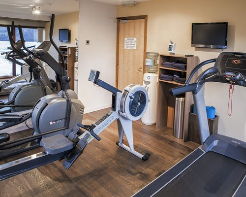 A well equipped indoor fitness area with television.