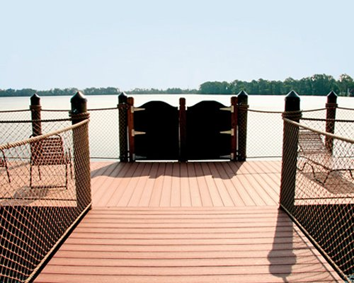 Wooden pathway with chaise lounge chairs leading to lake.