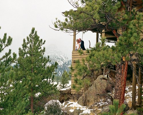 A couple in a balcony of a unit at Historic Crags Lodge surrounded by wooded area during winter.