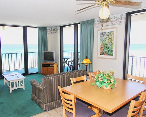 An open plan living room and dining area with a television balcony and ocean view.