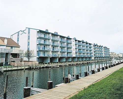 Exterior view of multiple balconies at The Quarters at Marlin Cove alongside a pathway and waterfront.