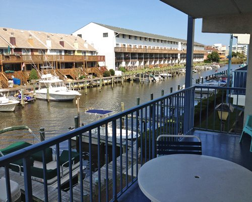 Balcony view of waterfront with boats at a marina alongside multiple unit balconies.