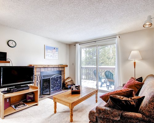 A well furnished living room with television fireplace balcony and patio chairs.