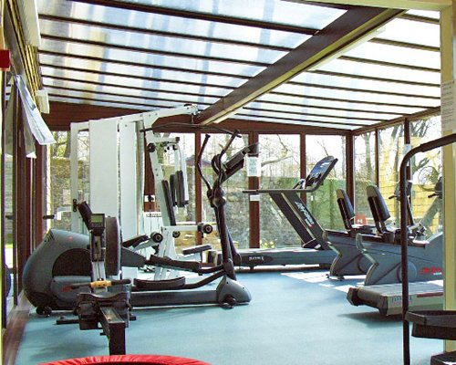 A well equipped indoor fitness area with an outside view.