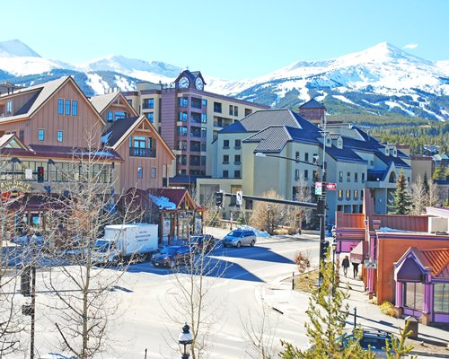 A street view of The Village at Breckenridge at the foothills of a mountain covered in snow.