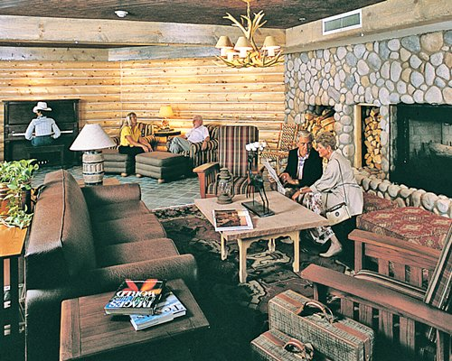 A well furnished living room wit fire place and a man playing piano.