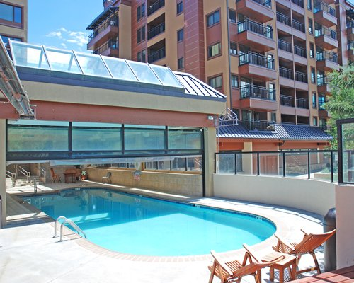 An outdoor swimming pool with patio furniture alongside multi story units.