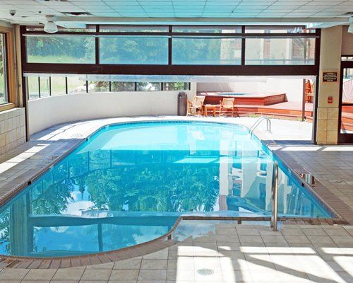 A view of indoor swimming pool and hot tub with patio furniture.
