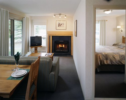 A well furnished living room with a television dining area fire in the fireplace and bedroom with queen bed.