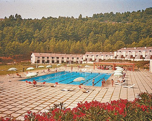 A view of an outdoor swimming pool alongside multi story units.