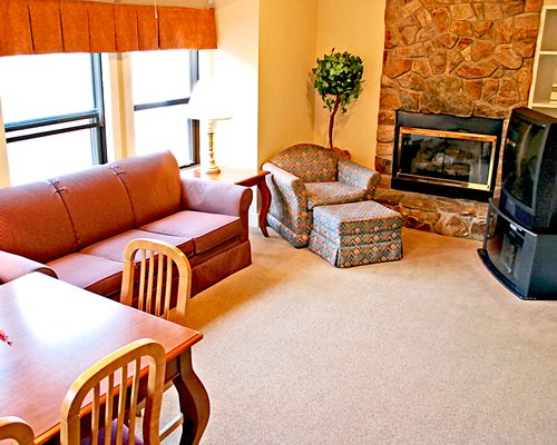 A well furnished living room with the television and fireplace.