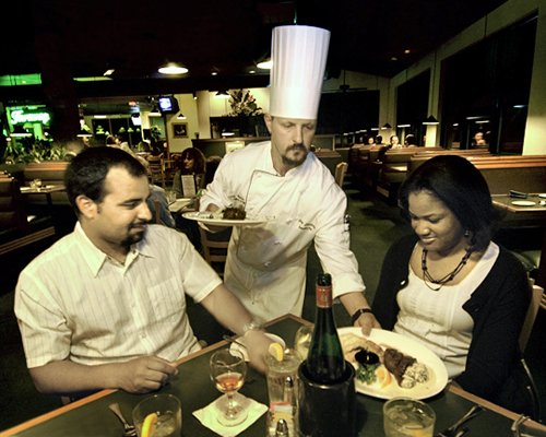 Chef serving food items to a couple at an indoor restaurant.