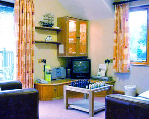 A well furnished living room with a television board game and outdoor view.
