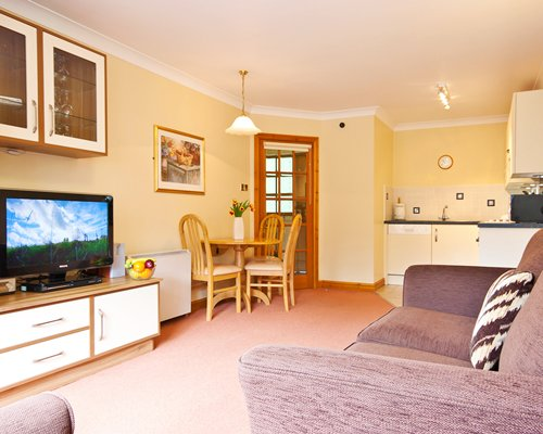 A well furnished living room with an open plan kitchen dining area and television.