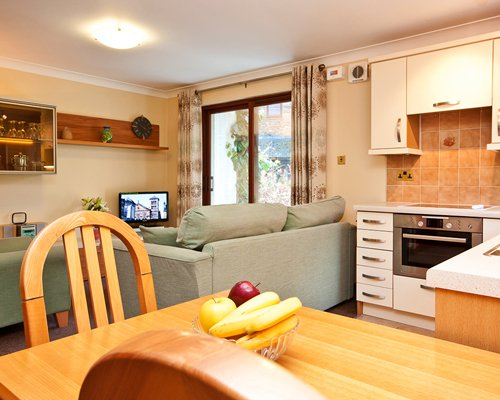 An open plan living dining and kitchen area with a television.