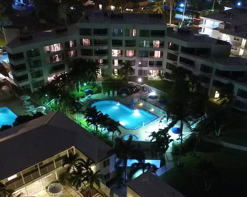 An aerial view of multi story resort units with balconies with a swimming pool at night.