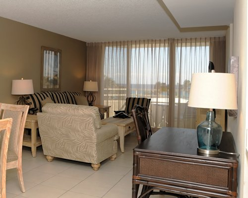 A well furnished bedroom with a dining area and outdoor view.