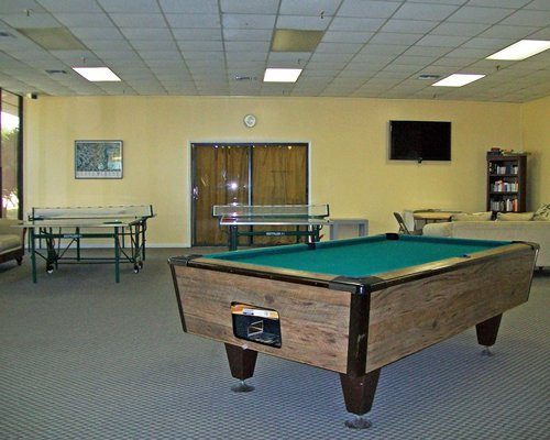 An indoor recreational room with pool and ping pong table.