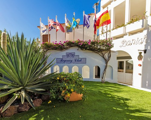 A scenic view of The Regency Club Tenerife resort with flags.