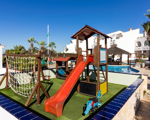 An outdoor playscape alongside swimming pool.