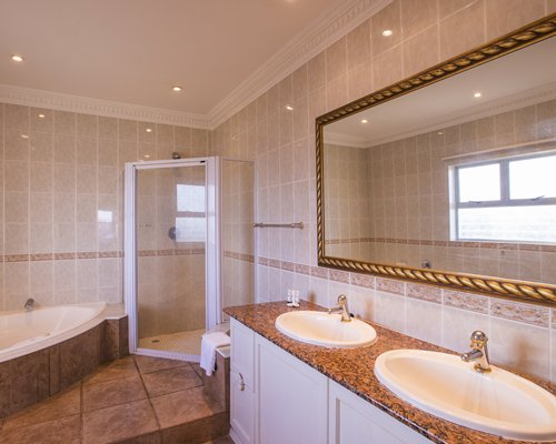 A bathroom with a shower bathtub and double sink vanity.