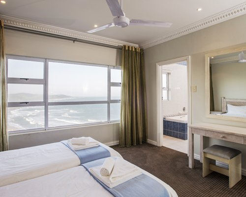 A well furnished bedroom with a vanity bathtub and an outside view.