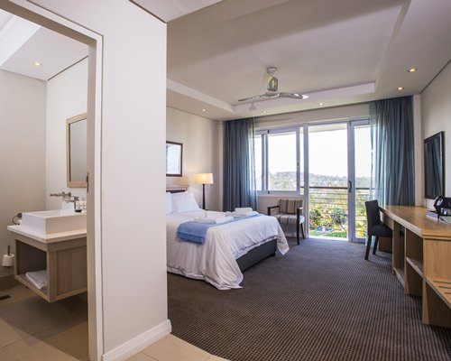 A well furnished bedroom with attached bathroom television and an outside view.
