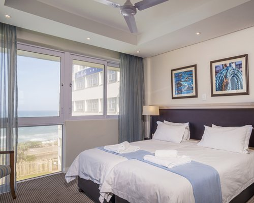 A well furnished bedroom with twin beds and beach view.