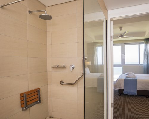 A bathroom with a shower stall alongside the bedroom.