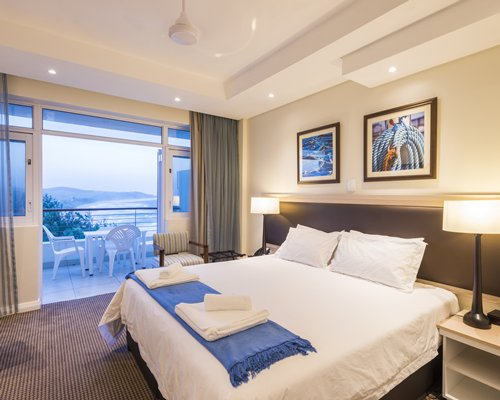 A well furnished bedroom with a balcony patio chairs and ocean view.