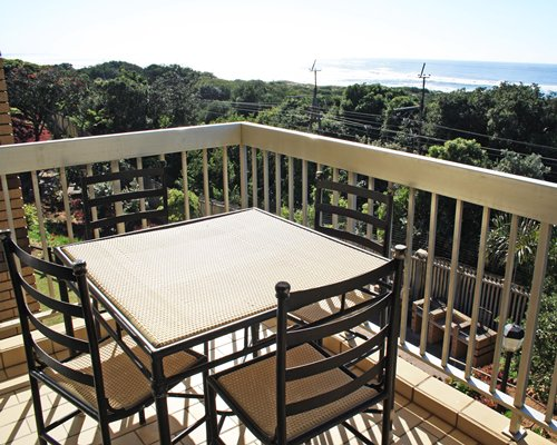 A balcony with a patio furniture facing an outside view.