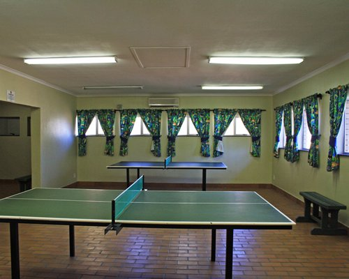 An indoor recreation room with two ping pong tables.