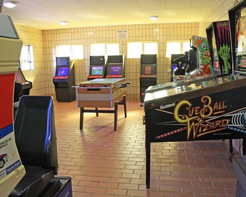 An indoor recreation room with soccer table and arcade games.