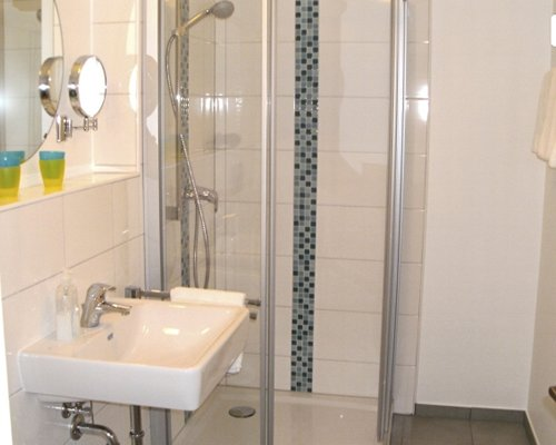 A bathroom with a stand up shower sink and mirror.