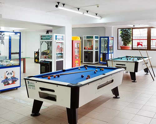 Indoor recreation room with arcade games and pool table.