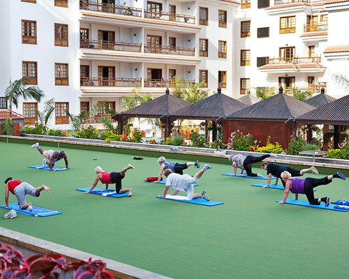 A group of people doing yoga alongside the resort.