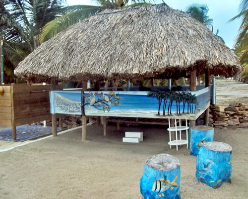 View of the thatched sunshade with trees on the beach.